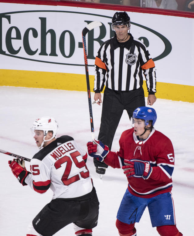 In this photo taken Sept. 17, 2018, referee Wes McCauley, top, keeps an eye on the play as the Montreal Canadiens face the New Jersey Devils during preseason NHL hockey game action in Montreal. An informal poll of NHL players leaves no doubt as to who the most popular referee is: Veteran McCauley. (Paul Chiasson/The Canadian Press via AP)
