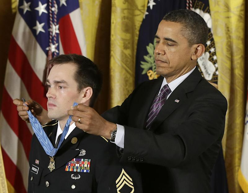 President Barack Obama bestows the Medal of Honor on retired Staff Sgt. Clinton Romesha for conspicuous gallantry, Monday, Feb. 11, 2013,  in the East Room of the White House in Washington. Romesha's leadership during a daylong attack by hundreds of fighters on Combat Outpost Keating in Afghanistan led to award. (AP Photo/Pablo Martinez Monsivais)