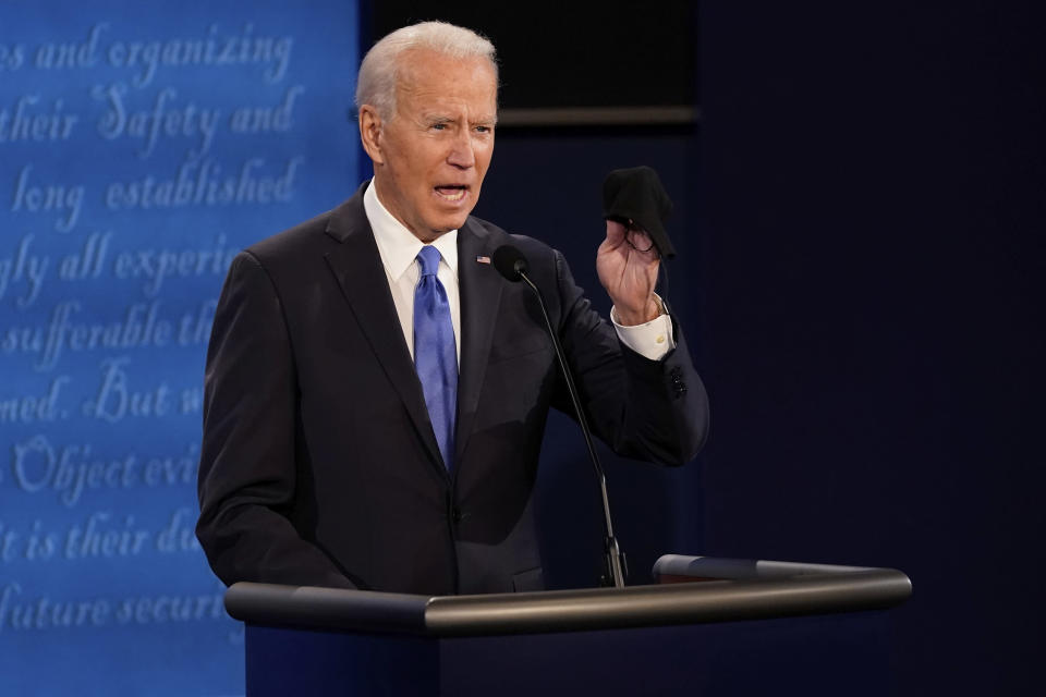 Democratic presidential candidate former Vice President Joe Biden holds up a mask during the second and final presidential debate Thursday, Oct. 22, 2020, at Belmont University in Nashville, Tenn. (AP Photo/Morry Gash, Pool)