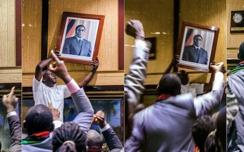 Images taken inside the conference centre where parliament was sitting show people removing pictures of Mr Mugabe - Credit:  JEKESAI NJIKIZANA/AFP