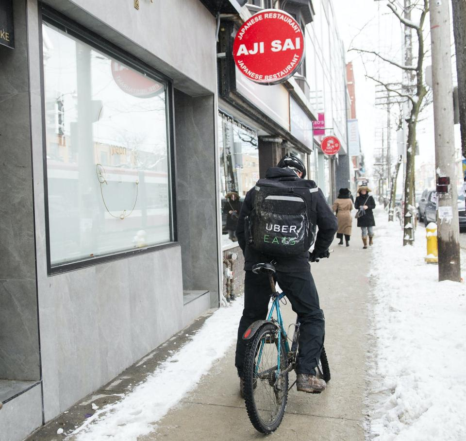 """<span class=""""caption"""">An Uber Eats courier pick ups an order for delivery from a restaurant in Toronto. </span> <span class=""""attribution""""><span class=""""source"""">THE CANADIAN PRESS/Nathan Denette</span></span>"""