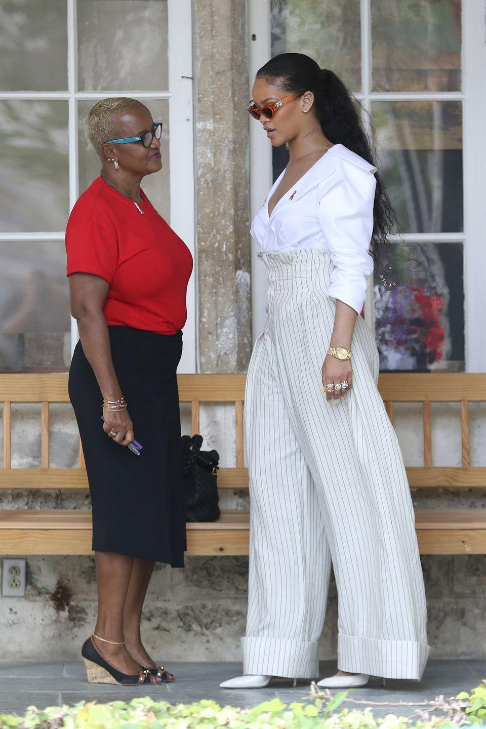 <p>In a white blazer top, ultra high waisted pin-striped trousers, white pointed-toe pumps, assorted rings, a gold watch and '90s-esque orange sunglasses in Barbados. </p>