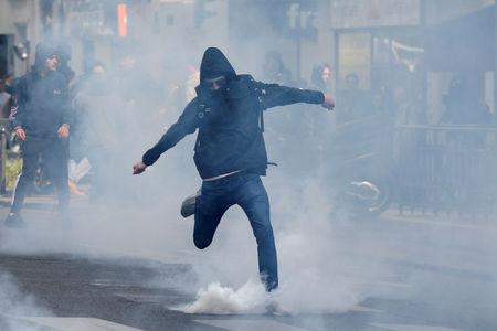 A hooded youth kicks a tear gas canister during a demonstration to protest the results of the first round of the presidential election in Paris