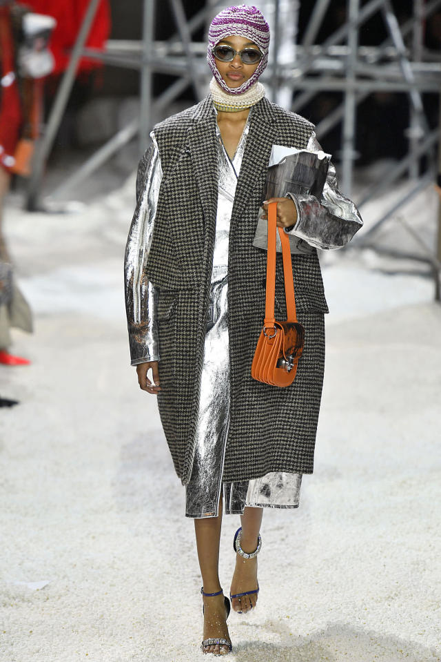 <p>A model wears a balaclava and a houndstooth sleeveless coat over a metallic-silver coat at the Calvin Klein fall 2018 show. (Photo: Getty Images) </p>
