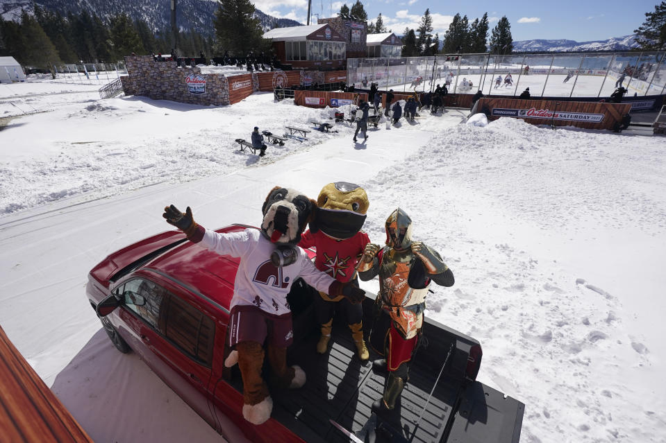 Bernie, the St. Bernard, left, the mascot of the Colorado Avalanche poses for photos with Vegas Golden Knights mascots, Chance, the Gila monster, center, and the Golden Knight, right, before the start of the Outdoor Lake Tahoe NHL hockey game between the two teams at Stateline, Nev., Saturday, Feb. 20, 2021. (AP Photo/Rich Pedroncelli))