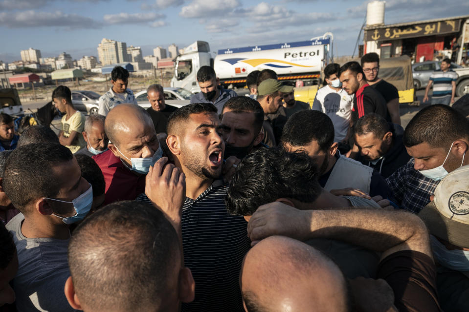 An auctioneer shouts numbers to recorders as the day's catch is sold to buyers after a limited number of fishing boats were allowed to return to the sea following a cease-fire reached after an 11-day war between Hamas and Israel, in Gaza City, Sunday, May 23, 2021. (AP Photo/John Minchillo)