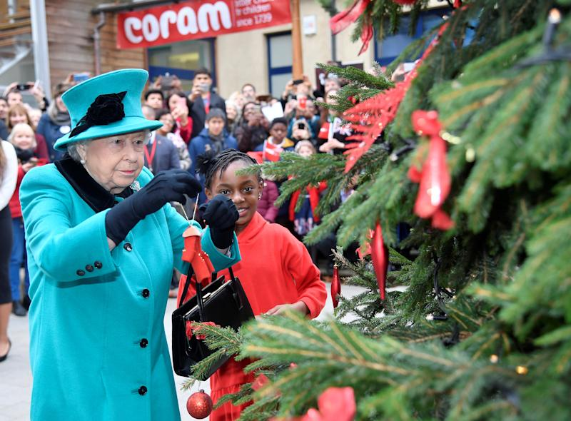 Queen Elizabeth II and Shylah Gordon, aged 8, attach a bauble to a Christmas tree during the opening of the Queen Elizabeth II centre at CORAM on December 05, 2018 in London, England.