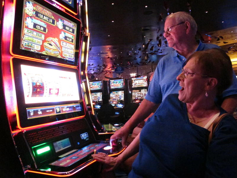 In this June 25, 2018 photo, Joyce Green of Vineland, N.J. reacts to a winning spin at a slot machine as her husband Tom looks on inside the Ocean Casino Resort in Atlantic City, N.J. The casino formerly known as Revel will turn a profit in May after months of steep losses. (AP Photo/Wayne Parry)