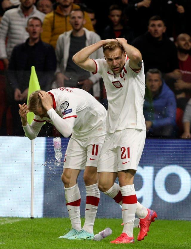 Poland's Karol Swiderski, left, holds his head as fans throw missiles onto the pitch following his goal