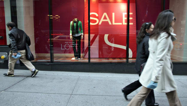 Pedestrians walk in front of large sale signs in the front w
