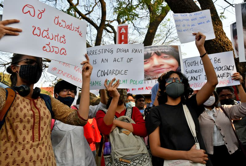 People hold placards during a protest against the arrest of 22-year-old climate activist Disha Ravi, in Bengaluru