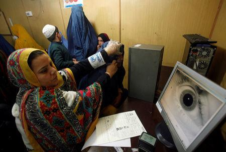 A UNHCR official carries out an IRIS test on an Afghan refugee at the United Nations High Commissioner for Refugees office on the outskirts of Peshawar