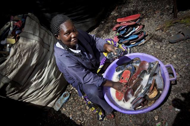 In this photo taken Monday, April 29, 2013, worker Jacqueline Achien washes discarded flip-flops in a bucket prior to them being sorted and carved into toy animals, at the Ocean Sole flip-flop recycling company in Nairobi, Kenya. The company is cleaning the East African country's beaches of used, washed-up flip-flops and the dirty pieces of rubber that were once cruising the Indian Ocean's currents are now being turned into colorful handmade giraffes, elephants and other toy animals. (AP Photo/Ben Curtis)