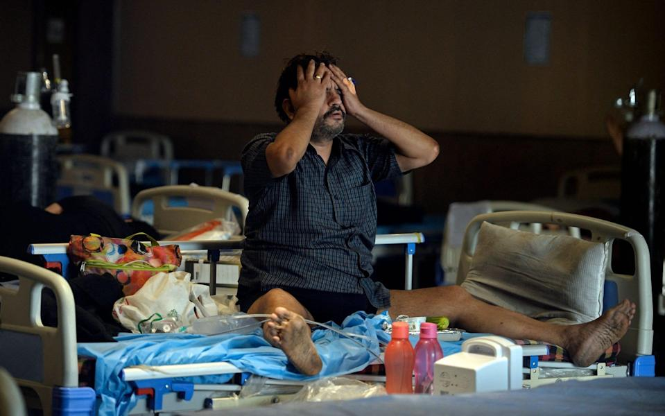 A Covid-19 coronavirus patient reacts while sitting on a bed inside a banquet hall temporarily converted into a Covid care centre in New Delhi - ARUN SANKAR/AFP
