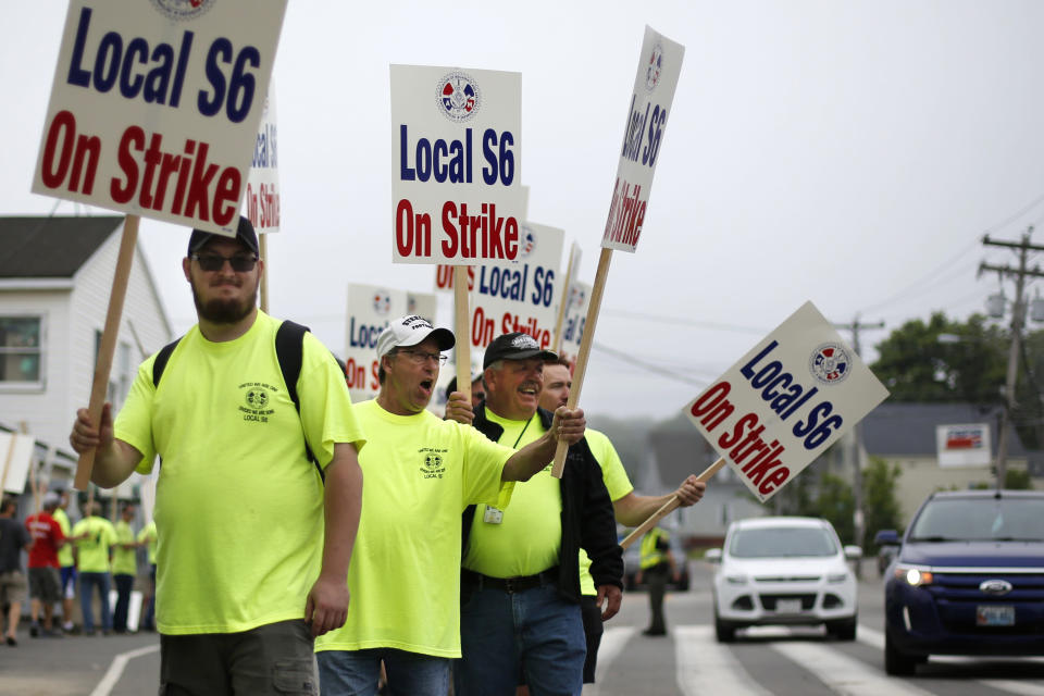 Picketers acknowledge a honking motorist outside an entrance to Bath Iron Works, Monday, June 22, 2020, in Bath, Maine. Production workers at one of the Navy's largest shipbuilders overwhelmingly voted to strike, rejecting the company's three-year contract offer Sunday and threatening to further delay delivery of ships. (AP Photo/Robert F. Bukaty)