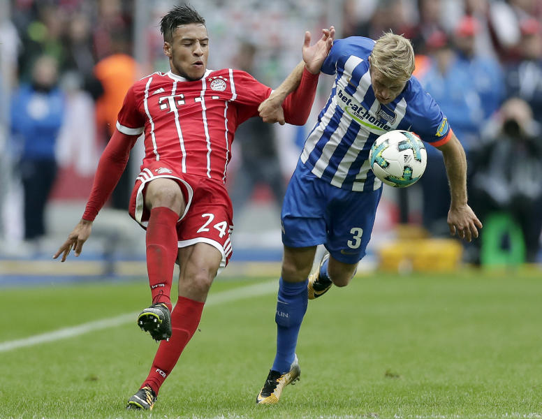 Bayern's Corentin Tolisso, left, and Hertha's Per Ciljan Skjelbred, right, challenge for the ball during the German Bundesliga soccer match between Hertha BSC Berlin and FC Bayern Munich in Berlin, Germany, Sunday, Oct. 1, 2017. The match ended in a 2-2 draw. (AP Photo/Michael Sohn)