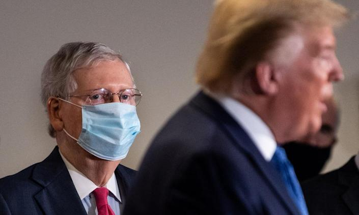 """<span class=""""element-image__caption"""">The Senate majority leader, Mitch McConnell, wears a mask this week as he listens to Donald Trump, who by contrast goes uncovered.</span> <span class=""""element-image__credit"""">Photograph: Kevin Dietsch/EPA</span>"""