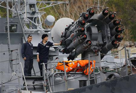 Sailors stand next to a weapons system onboard a Russian Navy vessel anchored at a navy base in the Ukrainian Black Sea port of Sevastopol in Crimea