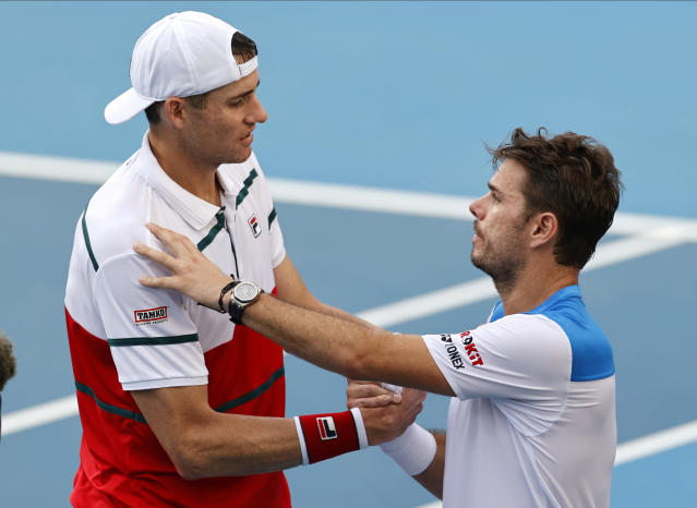 John Isner, left, of the U.S. shakes hands with Switzerland's Stan Wawrinka after retiring from their third round match at the Australian Open tennis championship in Melbourne, Australia, Saturday, Jan. 25, 2020. (AP Photo/Andy Wong)