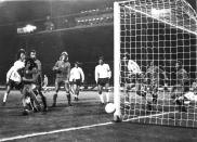 FILE - In this Oct. 17, 1973 file photo England's Mike Channon, left in white shirt, hits the ball past the post, in the final minutes of the World Cup qualifying soccer match against Poland, at Wembley Stadium London. The match ended in a 1-1 draw, which sent Poland into the World Cup Finals in Germany, in 1974. (AP Photo/Dave Caulkin, File)