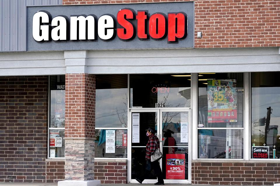 A woman wears a face mask as she walks past a GameStop store in Des Plaines, Ill., in this Oct. 15, 2020 file photo.