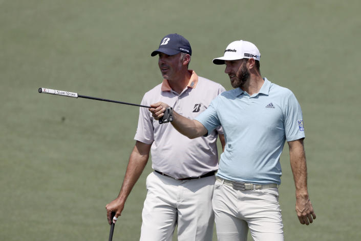 Dustin Johnson, right, and Matt Kuchar look over a shot on the second hole during a practice round for the Masters golf tournament at Augusta National Golf Club on Wednesday, April 7, 2021, in Augusta, Ga. (Curtis Compton/Atlanta Journal-Constitution via AP)