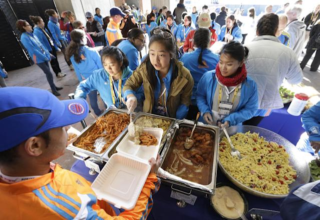Wellesley College student Tiffany Liao, of San Marino, Calif., center, serves a pasta dish during a Boston Marathon pre-race dinner at Boston City Hall, Sunday, April 20, 2014, in Boston. With an expanded field of runners and the memory of last year's bombings the 2014 Boston Marathon could bring an unprecedented wave of visitors to the area. (AP Photo/Steven Senne)