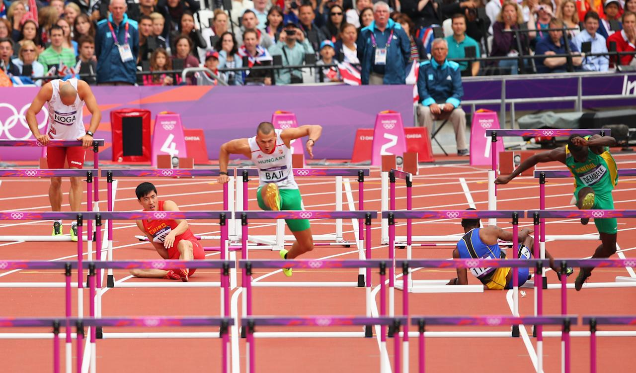 Balazs Baji of Hungary leads the pack as Xiang Liu of China falls over a hurdle in the Men's 110m Hurdles Round 1 Heats on Day 11 of the London 2012 Olympic Games at Olympic Stadium on August 7, 2012 in London, England.  (Photo by Cameron Spencer/Getty Images)