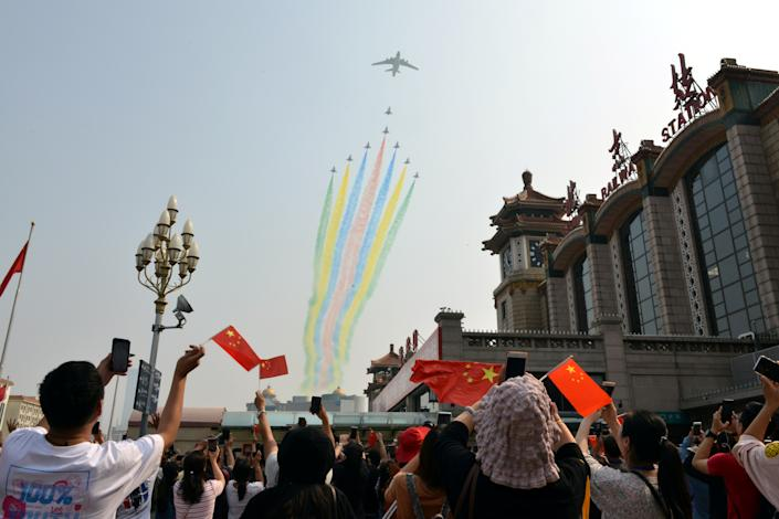 People hold their mobile phones and Chinese flags as military aircraft fly in formation during the military parade marking the 70th founding anniversary of People's Republic of China, at a railway station in Beijing, China October 1, 2019. (Photo: Tingshu Wang/Reuters)