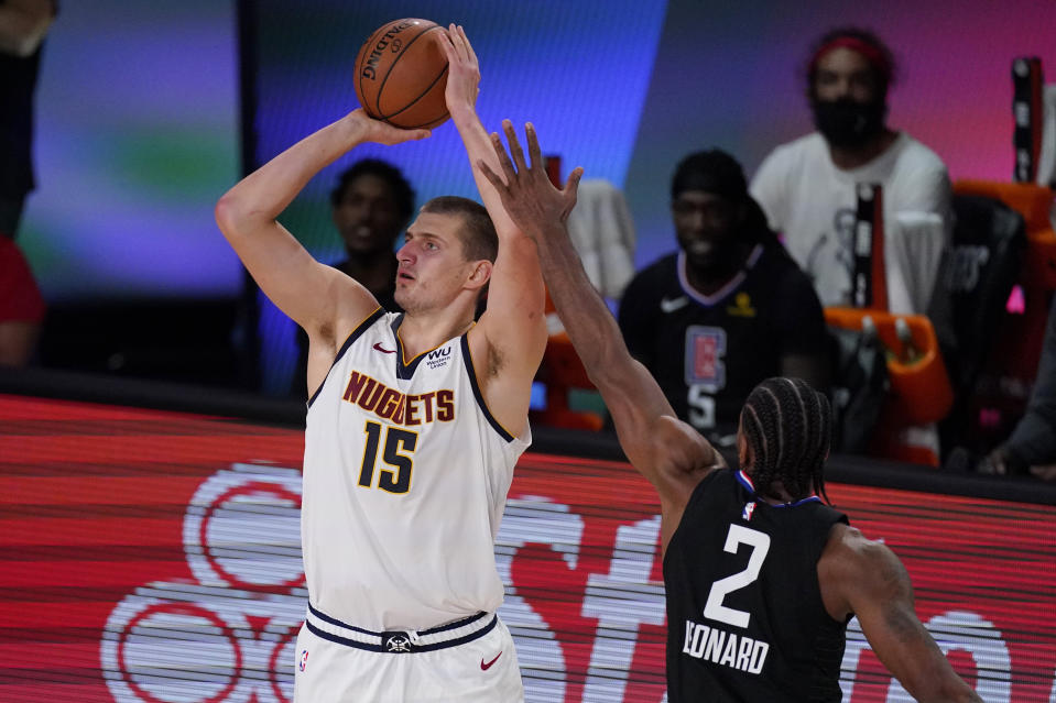 Denver Nuggets' Nikola Jokic (15) shoots in front of Los Angeles Clippers' Kawhi Leonard (2) in the second half of an NBA conference semifinal playoff basketball game Thursday, Sept 3, 2020, in Lake Buena Vista Fla. (AP Photo/Mark J. Terrill)