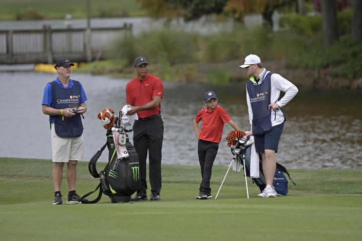 Tiger Woods, second from left, and his son Charlie wait to hit from the 18th fairway as caddies Joe LaCava, left, and Joe LaCava Jr., right, watch during the final round of the PNC Championship golf tournament, Sunday, Dec. 20, 2020, in Orlando, Fla. (AP Photo/Phelan M. Ebenhack)
