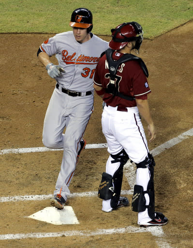 Arizona Diamondbacks catcher Wil Nieves waits for the throw as Baltimore Orioles' Taylor Teagarden scores on a two-run single by Nick Markakis during the second inning of a baseball game, Wednesday, Aug. 14, 2013, in Phoenix. (AP Photo/Matt York)