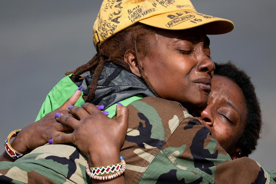 Phoenix Robles and Dorcas Monari hug each other near the Brooklyn Center Police Department in Minnesota after Robles, who was passing by, stopped to protect Monari, who was protesting in the street. (Nick Pfosi/Reuters)