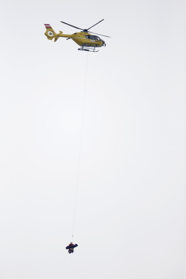 A helicopter transports United States' Lindsey Vonn off the slope after she fell during the women's super-G at the Alpine skiing world championships in Schladming, Austria, Tuesday, Feb.5,2013. (AP Photo/Matthias Schrader)