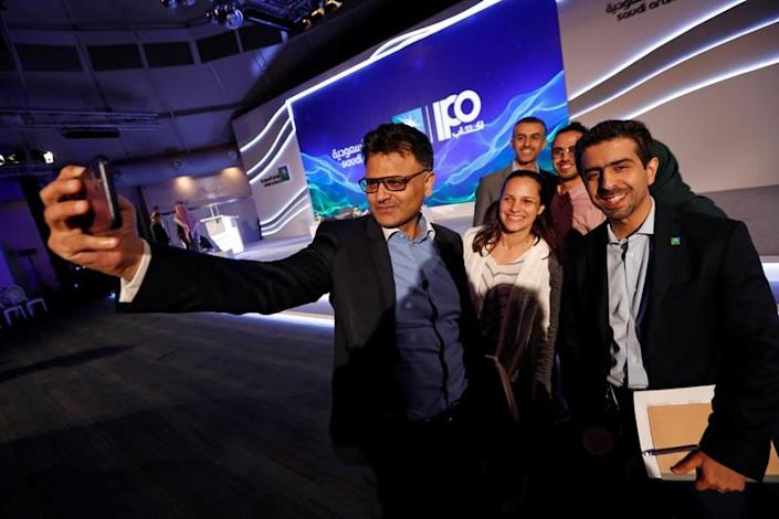 Saudi Aramco's IPO's team take a selfie after a news conference in Dhahran