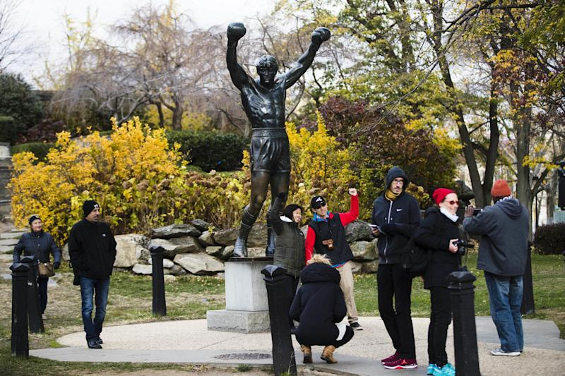 "Tourist visit a statue from the movie character Rocky Balboa outside the Philadelphia Museum of Art in Philadelphia, Monday, Nov. 21, 2016. Four decades after the Nov. 21, 1976, premiere of ""Rocky,"" the movie's reach is international, and the title character's underdog tale of determination, grit and sleepy-eyed charm still resonates with fans. (AP Photo/Matt Rourke)"