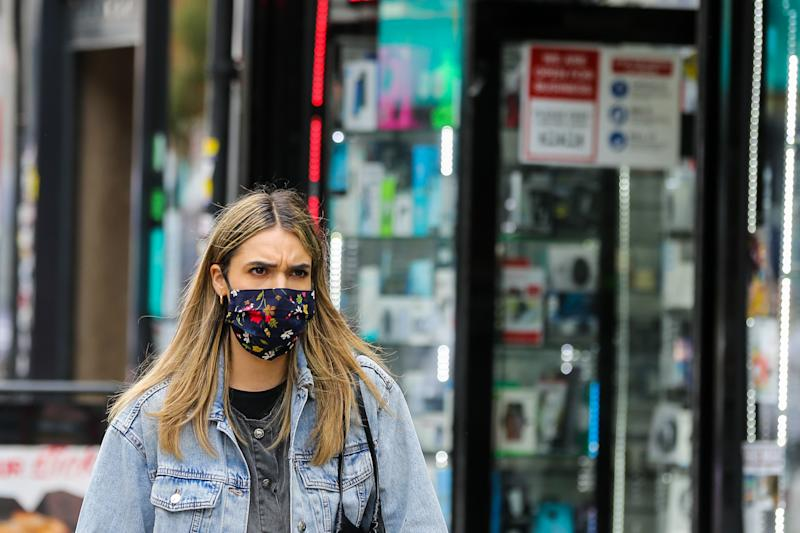 LONDON, UNITED KINGDOM - 2020/09/09: A woman wearing a face mask walks on the street. The number of people who tested positive for the coronavirus is increasing. (Photo by Dinendra Haria/SOPA Images/LightRocket via Getty Images)