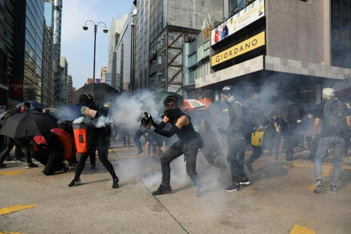 Protesters react after police fired tear gas in the Tsim Sha Tsui district of Hong Kong (AFP Photo/Dale DE LA REY)