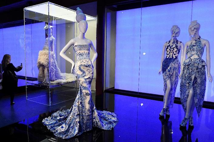 """A journalist takes photos of Chinese fashions displayed as part of """"China Through the Looking Glass"""" during a press preview May 4, 2015 at the Metropolitan Museum of Art in New York (AFP Photo/Don Emmert)"""