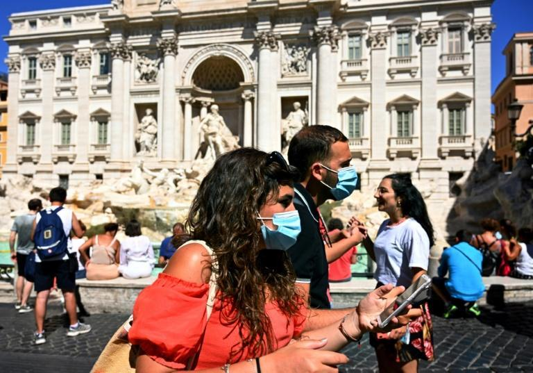 Tourists wearing face masks walk by the Trevi fountain in Rome. Italy, France, Spain and Germany have seen a spike in virus cases as the pandemic rebounds across Europe -- often due to travel, summer holidays and parties