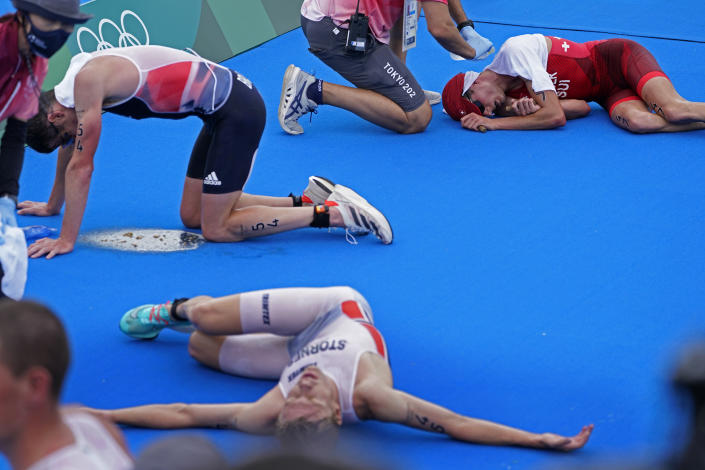 <p>Casper Stornes of Norway (45), Jonathan Brownlee of Great Britain (54) and Max Studer of Switzerland (47) all collapse after crossing the finish line at the men's individual triathlon during the 2020 Summer Olympics, Monday, July 26, 2021, in Tokyo, Japan. (AP Photo/David Goldman)</p>
