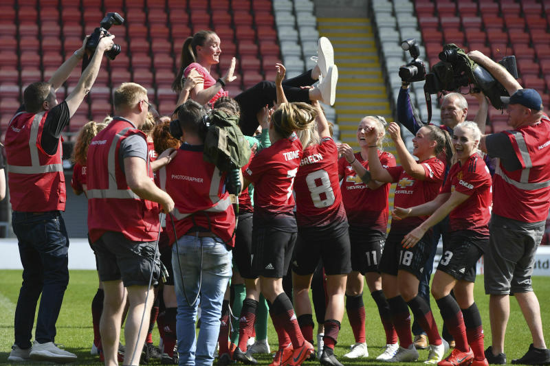 Manchester United manager Casey Stoney, top, is congratulated by players after the final whistle during the FA Women's Championship soccer match between Manchester United and Crystal Palace at Leigh Sports Village, Manchester, England, Saturday April 20, 2019. (Anthony Devlin/PA via AP)
