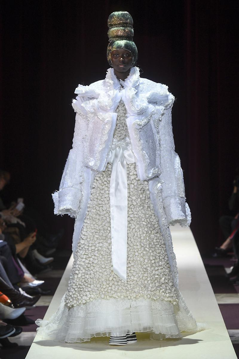 Image result for Comme des Garçons Rei Kawakubo offered a rock 'n' roll interpretation of the princess bride, complete with a band jacket crafted from padded lace and towering platform boots that were nothing short of extravagant.