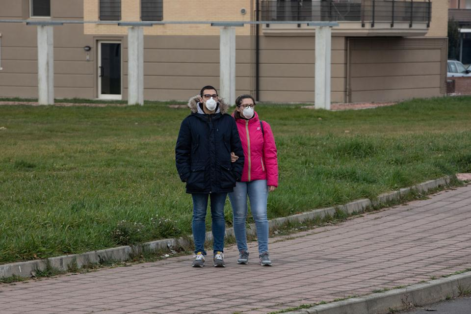 CASALPUSTERLENGO, ITALY - FEBRUARY 23: A couple, wearing a respiratory mask, stands on February 23, 2020 in Casalpusterlengo, south-west Milan, Italy. Casalpusterlengo is one of the ten small towns placed under lockdown earlier this morning as a second death from coronavirus sparked fears throughout the Lombardy region. (Photo by Emanuele Cremaschi/Getty Images)