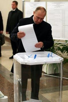 Putin holds a ballot paper as he votes at a polling station on Sept. 18, 2016 in Moscow