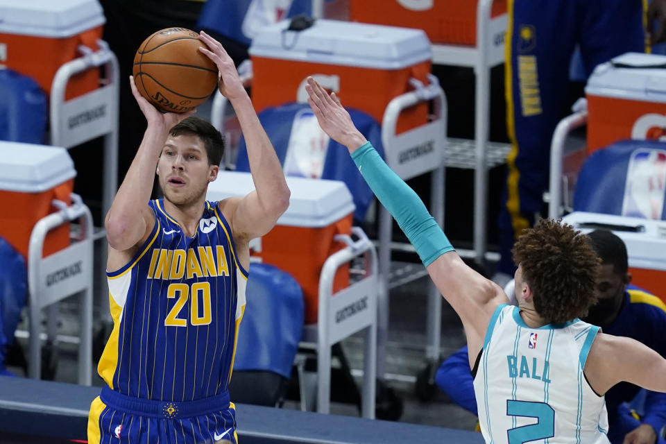 Indiana Pacers' Doug McDermott (20) shoots against Charlotte Hornets' LaMelo Ball (2) during the first half of an NBA basketball Eastern Conference play-in game Tuesday, May 18, 2021, in Indianapolis. (AP Photo/Darron Cummings)