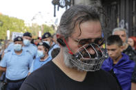A man wears a muzzle during a protest in Bucharest, Romania, Saturday, Sept. 19, 2020. Several hundred Romanians, including many families with young children, held a protest in the country's capital against measures meant to curb the spread of the coronavirus, especially social distancing and the mandatory use of masks in schools. (AP Photo/Vadim Ghirda)