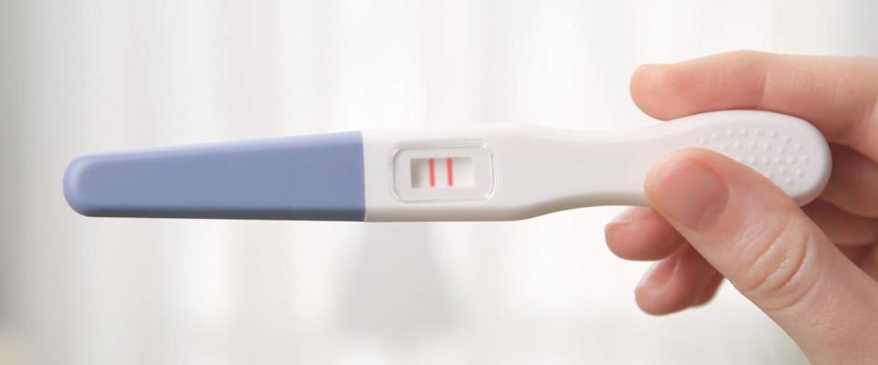 Pregnancy test in female hand on blurred background