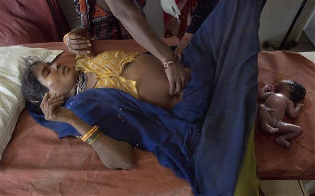 Anguri, a 26-year-old woman in labour, lies on a maternity table as she gives birth to a baby girl at a community health centre in the remote village of Chharchh, in the central Indian state of Madhya Pradesh, February 24, 2012.