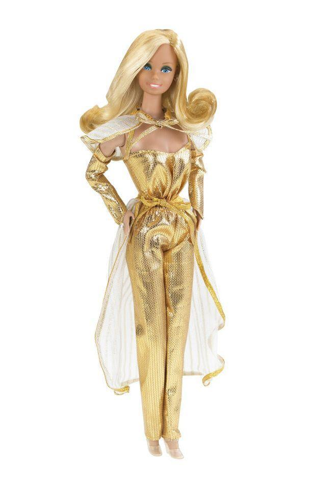 <p>Golden Dream Barbie goes in a very metallic direction, with an ensemble that brings together a strapless jumpsuit, opera-length globes, a sheer capelet and a sheer overskirt. </p>